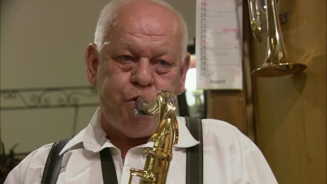 cu senior man playing saxophone in hofbrauhaus, munich, bavaria, germany - saxophone stock videos and b-roll footage