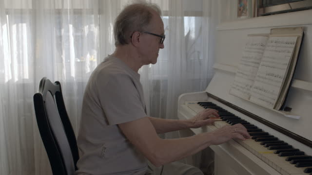 senior man playing the piano. - pianist stock videos & royalty-free footage