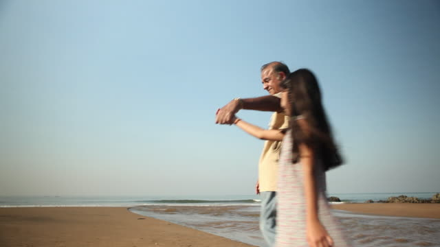 senior man playing with his granddaughter on the beach  - exhilaration stock videos and b-roll footage