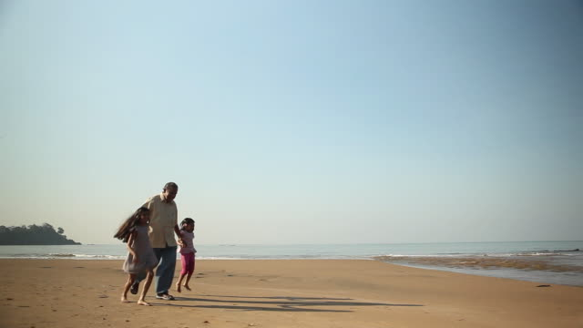Senior man playing with his granddaughters on the beach