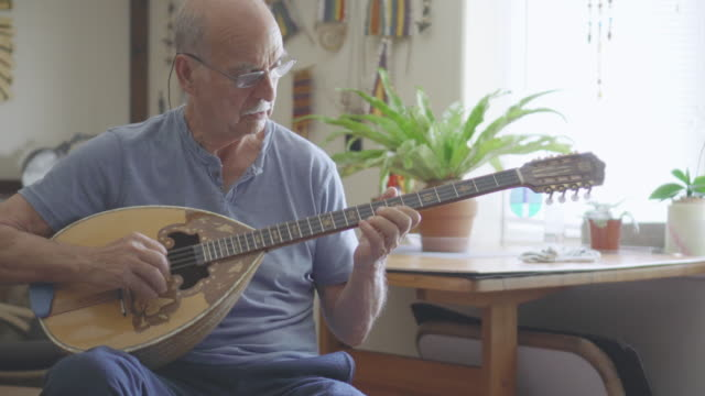 senior man plays a musical instrument - stringed instrument stock videos & royalty-free footage