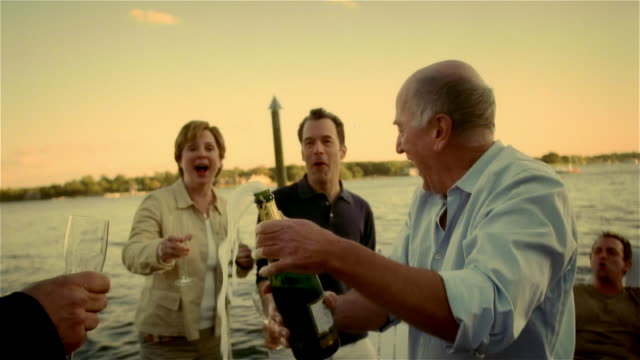 Senior man popping open bottle of champagne and pouring champagne into flutes for men and woman on lakeside dock