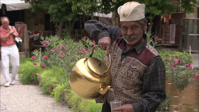 stockvideo's en b-roll-footage met ms senior man pouring water from large tea pot into plastic cup outdoors, iran - tuinpad