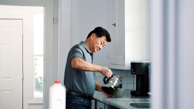 senior man pours morning cup of coffee - bricco per il caffè video stock e b–roll