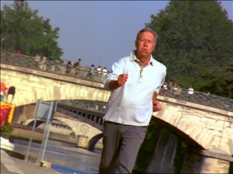 senior man power walking on sidewalk along seine / notre dame in background / paris, france - racewalking stock videos and b-roll footage