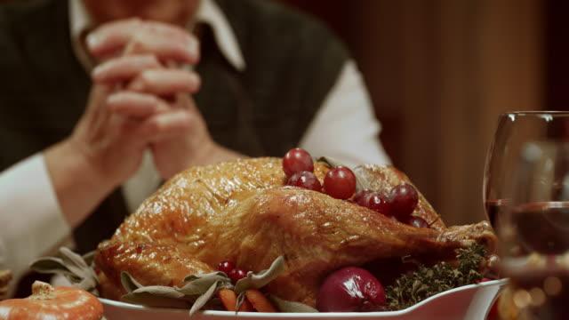 Senior man praying at Thanksgiving table before eating