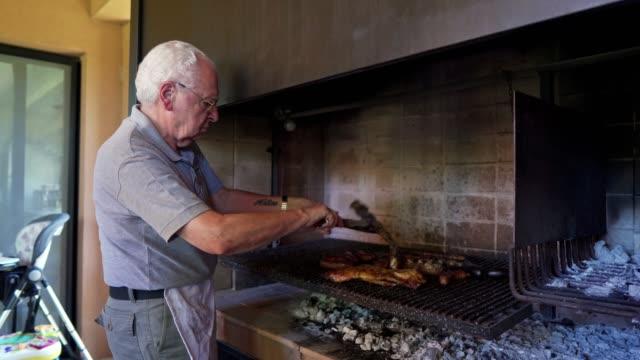 vídeos de stock e filmes b-roll de senior man preparing argentinian asado - gaúcho