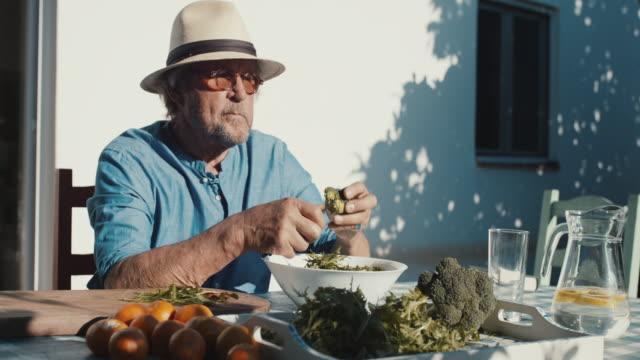 Senior man preparing salad, cutting broccoli outside in sun