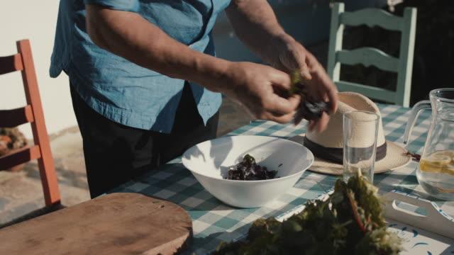 Senior man preparing salad outside in sun