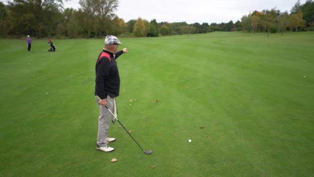 vídeos de stock, filmes e b-roll de a senior man preparing to drive the ball from the fairway. - bolsa de golfe