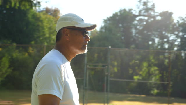 ts senior man preparing to serve during mixed doubles tennis match on summer morning - patience stock videos & royalty-free footage