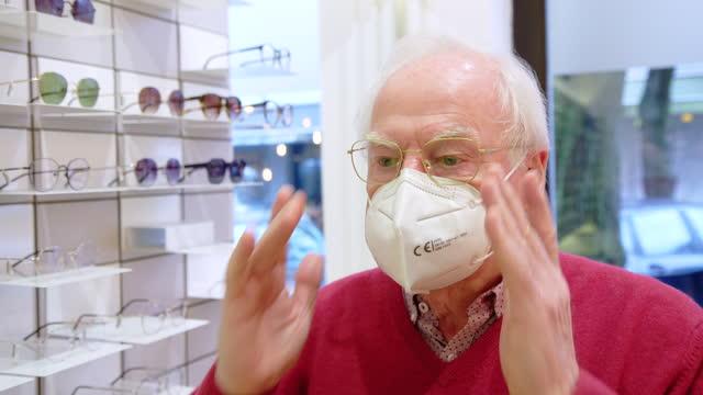 senior man purchasing new eyeglasses in optical store during pandemic - adjusting stock videos & royalty-free footage