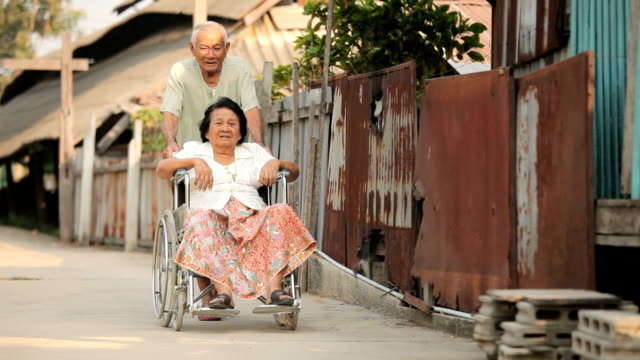 Senior man pushing her disabled wife on wheelchair