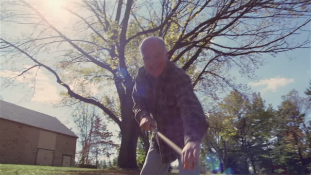 senior man raking leaves enthusiastically in back yard - 60 64 jahre stock-videos und b-roll-filmmaterial