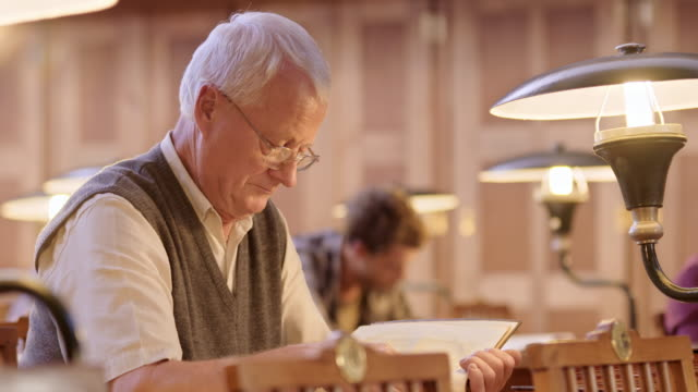 ld senior man reading a book in library - reading glasses stock videos & royalty-free footage