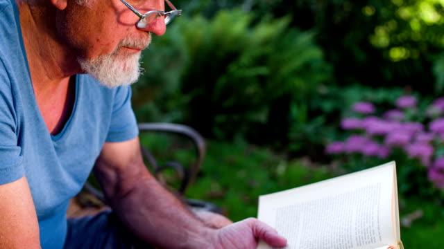 Hombre mayor leyendo un libro al aire libre
