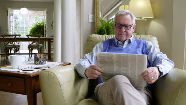 senior man reading a newspaper at home - cross legged stock videos & royalty-free footage