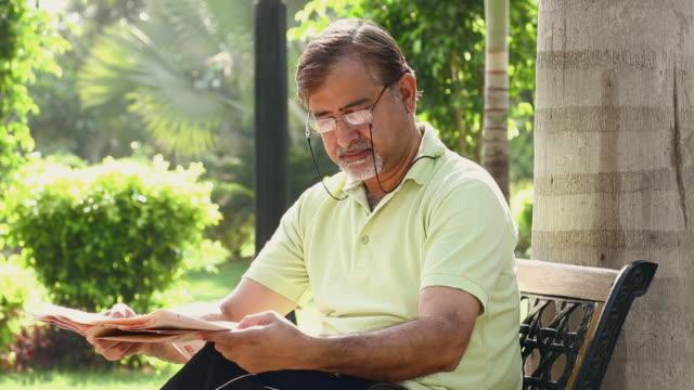 Senior man reading a newspaper in the park, Delhi, India