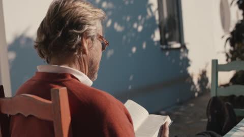 senior man reading book, enjoying sunshine - koncentration bildbanksvideor och videomaterial från bakom kulisserna