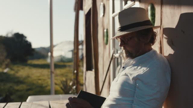 senior man reading book in sunshine - literature stock videos & royalty-free footage