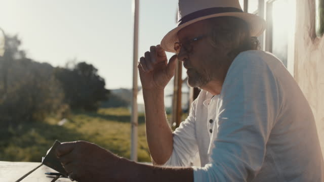 senior man reading book in sunshine - portugal stock videos & royalty-free footage
