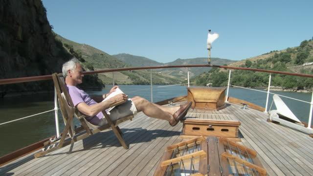 vídeos de stock, filmes e b-roll de senior man reading book on a boat - espreguiçadeira
