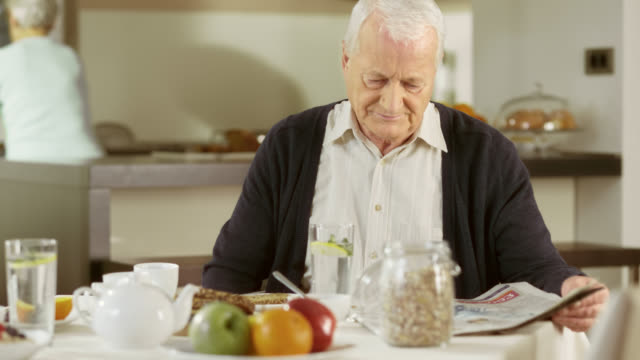 Senior man reading his newspaper at breakfast table