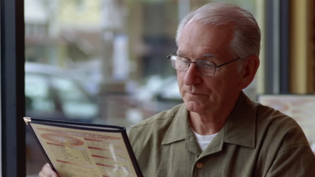 cu, senior man reading menu in diner  - demanding stock videos & royalty-free footage