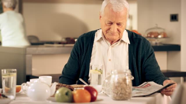 Alter Mann lesen Zeitung am Tisch für Frühstück