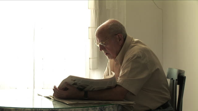 ms senior man reading newspaper at table, bilbao, spain - old newspaper stock videos and b-roll footage
