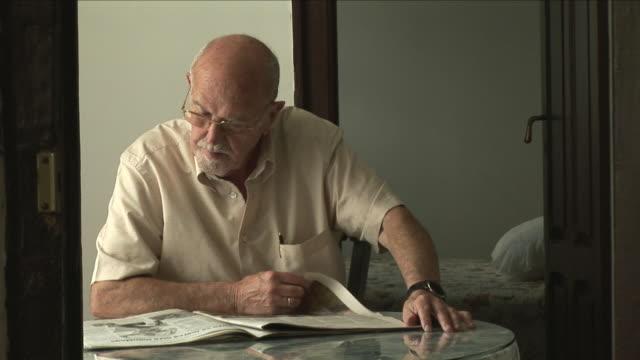 ms senior man reading newspaper at table, bilbao, spain - blick nach unten stock-videos und b-roll-filmmaterial