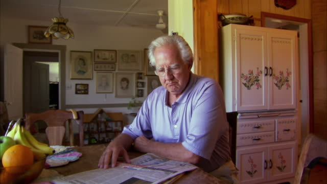 ms pan senior man reading newspaper in living room, halifax, nova scotia, canada - senior men stock videos & royalty-free footage