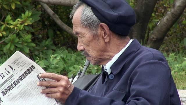 vidéos et rushes de cu senior man reading newspaper, lijiang, china - chinois