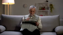 Senior man reading newspaper with magnifier, sitting on couch, eyesight problems