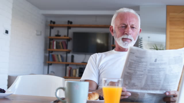 Senior man reads newspaper