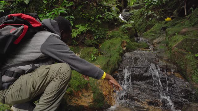 senior man refreshing on a stream during hiking - wilderness stock videos & royalty-free footage
