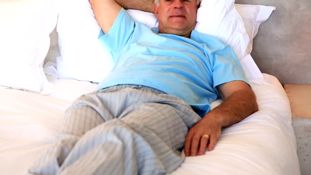 vídeos y material grabado en eventos de stock de senior hombre relajante en su cama - pijama