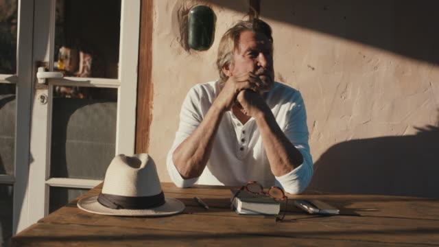 senior man relaxing on patio in sun - 休息 個影片檔及 b 捲影像