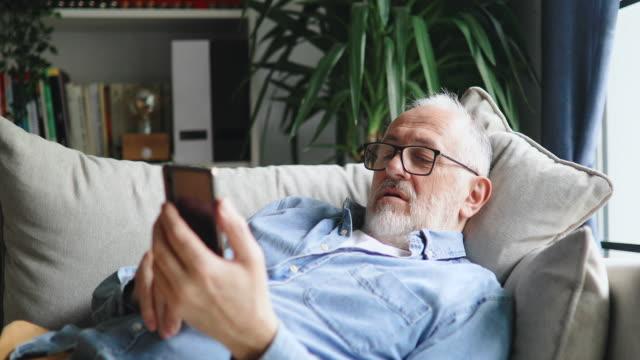 stockvideo's en b-roll-footage met hogere mens die op de bank ontspant en nieuws op zijn smartphone leest - publicatie