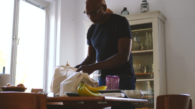 Senior man removing groceries from bag at dining table