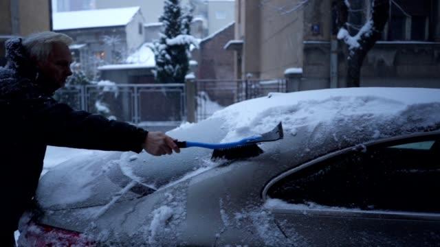 vídeos y material grabado en eventos de stock de senior hombre quitando la nieve de su coche - abrigo de invierno