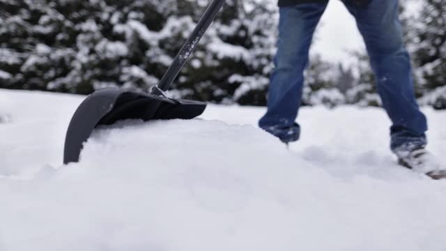 vídeos de stock e filmes b-roll de senior man removing snow from the backyard - pá para neve