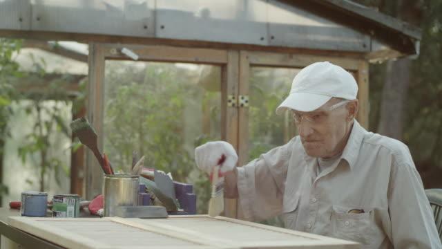 senior man renovating old furniture - greenhouse stock videos & royalty-free footage