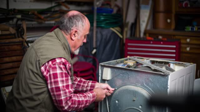 diy - senior man repairing a dryer - tumble dryer stock videos & royalty-free footage