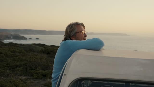 senior man resting on car looking at sunset - active seniors stock videos & royalty-free footage
