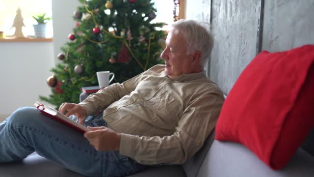 vídeos de stock, filmes e b-roll de idoso descansando no sofá e lendo livro em casa - idoso na internet