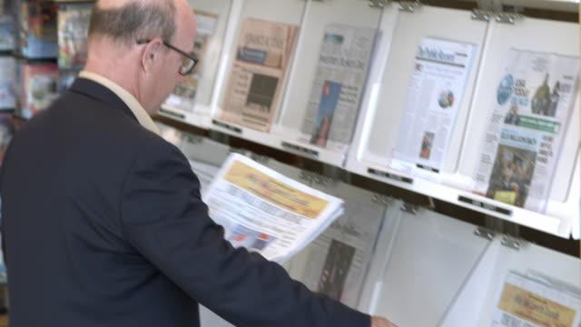 cu pan senior man retrieves financial newspaper from display rack at public library / rancho mirage, california, usa - rancho mirage stock videos & royalty-free footage