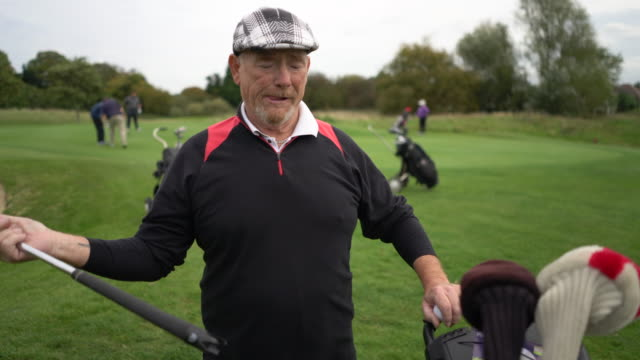 A senior man returning his putter to his bag.