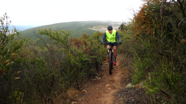 vidéos et rushes de ms senior man riding mountain bike on trail with friend on lush hillside - faire du vélo tout terrain
