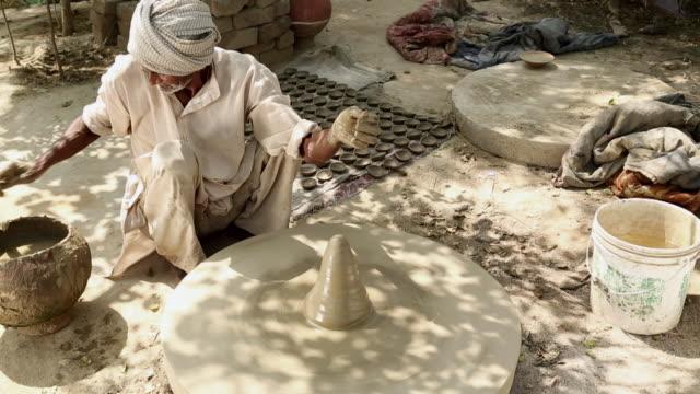 vídeos y material grabado en eventos de stock de senior man rotating clay pot, haryana, india - manos ahuecadas